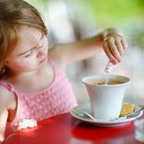Little girl pouring sugar into hot chocolate Royalty Free Stock Images