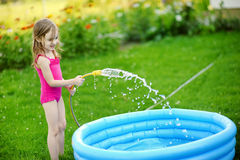 Little girl pouring water into a pool Royalty Free Stock Photo