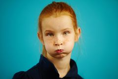 Little girl with pouty mouth and surprised look isolated on blue background. Red-haired child with freckles depicts an offended emotion Stock Image