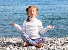 A little girl practices yoga and meditates in the lotus position on the pebble beach. Royalty Free Stock Image