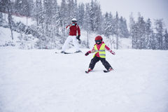Little girl practicing skiing and her mother filming here Stock Images