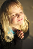 Little girl praying. A cute little girl with hands together in prayer royalty free stock image