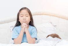 Little girl praying on bed, spirituality and religion. Little girl praying on bed. Little asian girl hand praying, Hands folded in prayer concept for faith Royalty Free Stock Photo