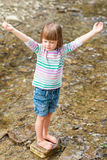 Little girl praying. Cute little barefoot girl praying - standing in a mountain stream royalty free stock photos