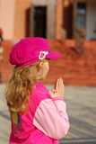 Little girl praying in front of church Royalty Free Stock Image