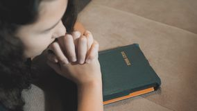 Little girl praying in the night. Little girl hand praying. little girl holy bible prays with bible in her hands. the