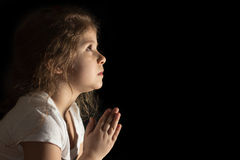 Little girl praying. To God divine light put your hands in prayer Stock Photos