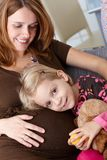 Little girl and pregnant mother smiling Stock Photo