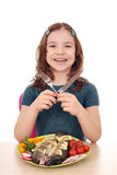 Little girl with prepared fish on table Royalty Free Stock Image