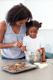 Little girl preparing biscuits with her mother Royalty Free Stock Photo
