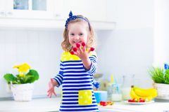 Little girl preparing breakfast in a white kitchen Stock Photos