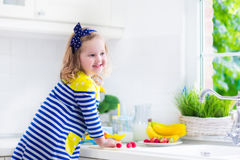 Little girl preparing breakfast in a white kitchen Royalty Free Stock Photography