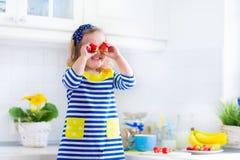 Little girl preparing breakfast in a white kitchen Stock Image