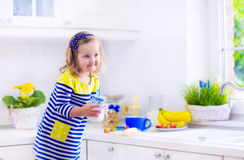 Little girl preparing breakfast in a white kitchen Royalty Free Stock Images