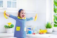 Little girl preparing breakfast in a white kitchen Stock Photography