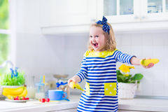 Little girl preparing breakfast in a white kitchen Royalty Free Stock Photos