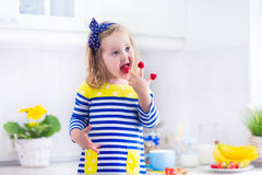 Little girl preparing breakfast in a white kitchen Royalty Free Stock Photo