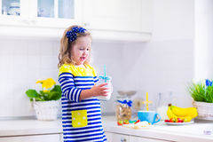 Little girl preparing breakfast in a white kitchen Stock Image