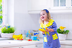Little girl preparing breakfast in a white kitchen Royalty Free Stock Photo