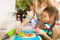 Little girl preparing a cookie on kitchen for her mother. Family, children cooking and help concept royalty free stock image