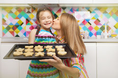 Little girl preparing a cookie on kitchen for her mother. Family, children cooking and help concept stock photography