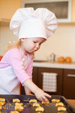 Little girl preparing cookies on kitchen Stock Images