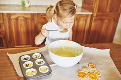 A little girl is preparing a dough for muffins. royalty free stock photo