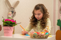 Little girl preparing for Easter - painting, drawing colored in the Room Royalty Free Stock Photo