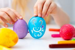 Little girl is preparing for Easter and painting eggs. Colorful markers. Rabbit template pattern.  stock photography