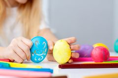 Little girl is preparing for Easter and painting eggs. Colorful markers. Rabbit template pattern.  royalty free stock image