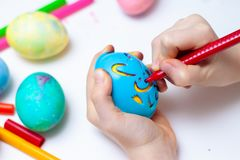 Little girl is preparing for Easter and painting eggs. Colorful markers. Rabbit template pattern.  royalty free stock photography