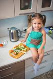 Little girl preparing salad in the kitchen. At home Stock Photo