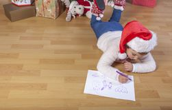 Little girl preparing the Santa Letter. She painting the gifts s. He want. Pre-reader concept Stock Photos