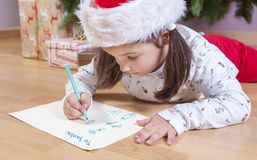 Little girl preparing The Santa Letter. She painting a sheet with header in English Stock Photography
