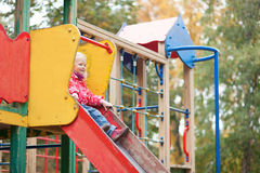 Little girl preparing to slither from a slide Stock Image