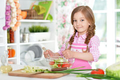 Little girl preparing vegetable salad. Cute little girl preparing vegetable salad in kitchen Stock Image
