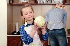 Little girl is preparing vegetables for salad closeup Stock Images