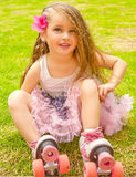 Little girl preschool beginner in roller skates, in a grass background Royalty Free Stock Photos