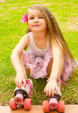 Little girl preschool beginner sitting in the grass with her roller skates, in a grass background Royalty Free Stock Images