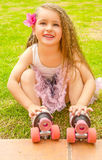 Little girl preschool beginner sitting in the grass with her roller skates, in a grass background Stock Image