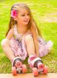 Little girl preschool beginner sitting in the grass with her roller skates, in a grass background Royalty Free Stock Photo