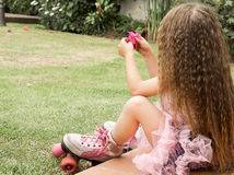 Little girl preschool sitting on ground wearing her roller skates, in a garden background, back view Stock Images