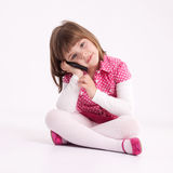 Little girl preschooler model. In pink skirt, sandals and dotted shirt and sitting on the floor with mobile phone Royalty Free Stock Images