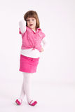Little girl preschooler model. In pink skirt, sandals and dotted shirt and standing with mobile phone Stock Photo