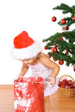 Little girl with present and christmas tree royalty free stock image