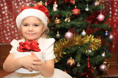 The little  girl with a present near fir-tree Stock Images