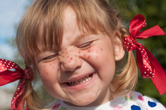 A little girl presenting Pippi Longstocking with her eyes closed and making faces. A funny cute outdoor close up portrait of a little girl presenting Pippi stock photography