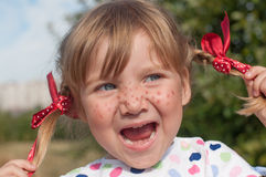 A little girl presenting Pippi Longstocking with her eyes closed and making faces Stock Images