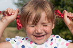 A little girl presenting Pippi Longstocking with her eyes closed and making faces Royalty Free Stock Photos