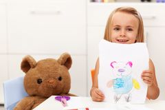 Little girl presents her drawing - a portrait of her toy bear Stock Image